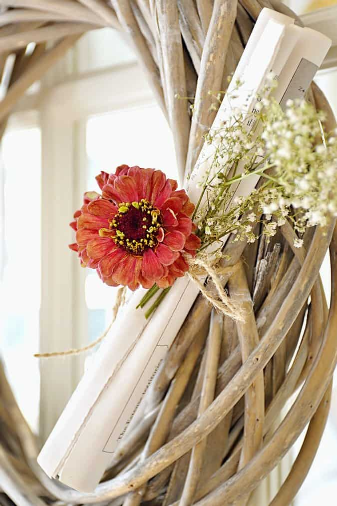 Woven wooden wreath with book pages and flowers.