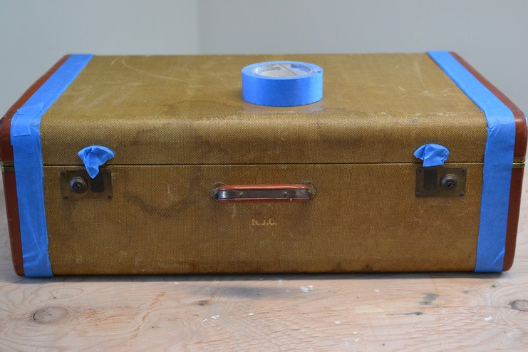 Vintage suitcase taped up for painting.