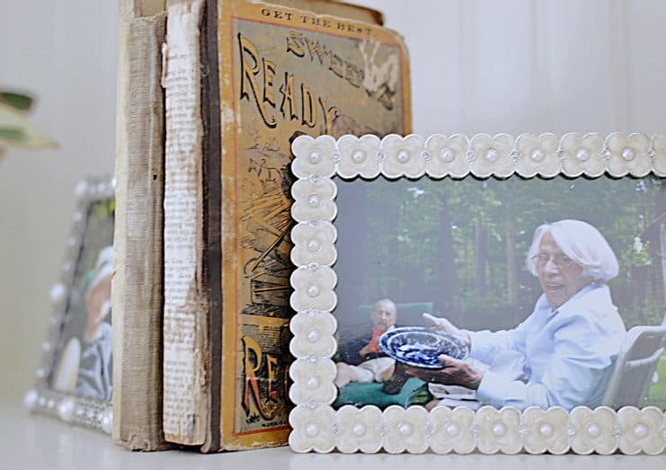 Vintage books with picture frames as bookends.