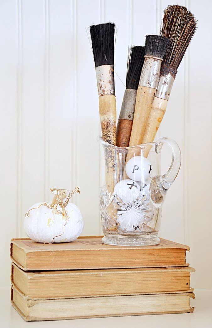 Vintage paintbrushes, letter balls, books and white pumpkin