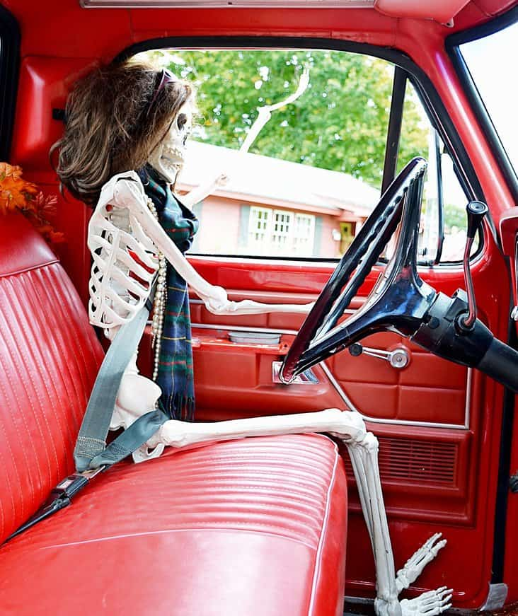 Female halloween skeleton waving out of vintage ford truck