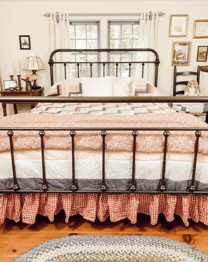 rod iron bed with vintage bedding.