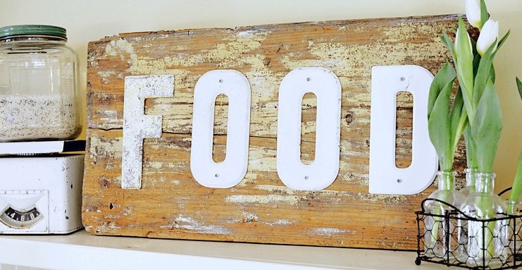 Vintage wooden FOOD sign on top kitchen shelf.