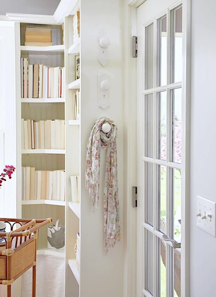 Porcelan white door knob wall hangers and bookshelves w/ books.