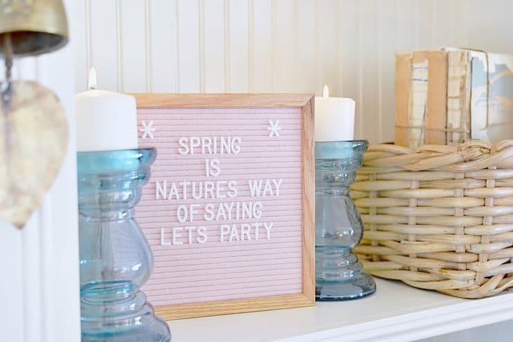 Pink felt letter board, blue candle glass candlesticks, basket, vintage books in a white built in shelving