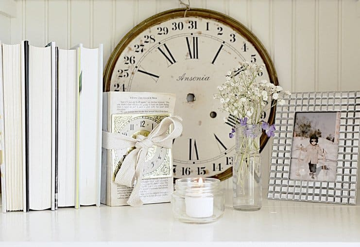 Decorated bookshelf with vintage finds clock face, books candle pictures and more.
