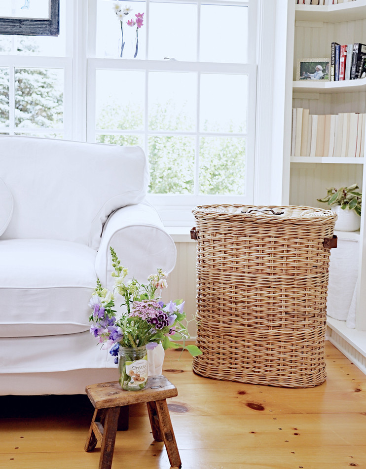 Sunroom makeover w/ builtins, basket white loveseat and market flowers with vintage flair.