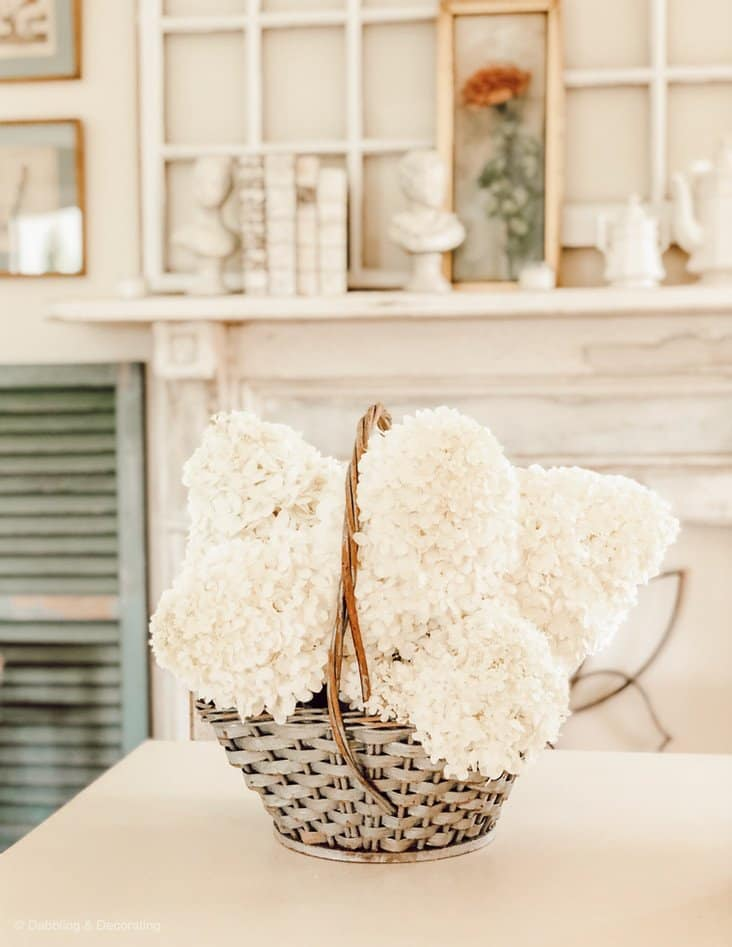 blue basket with white hydrangeas and a mantel.