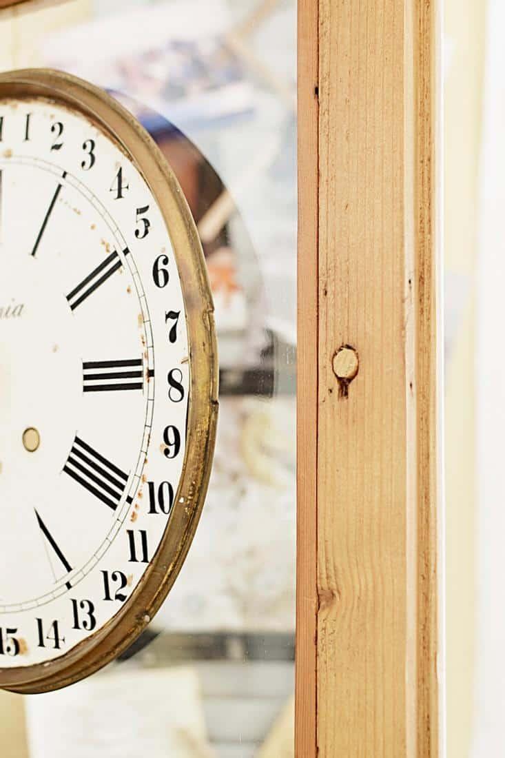 Vintage clock face on vintage wooden hutch glass door.