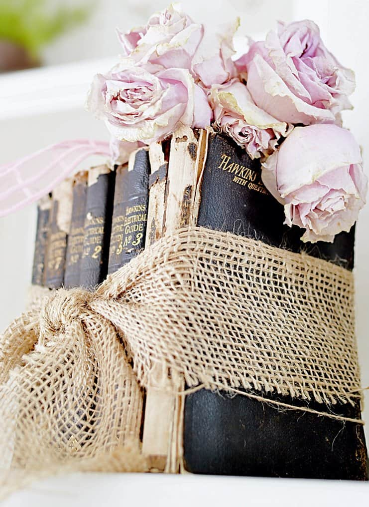 Vintage black books with dried pale pink roses and burlap bow.