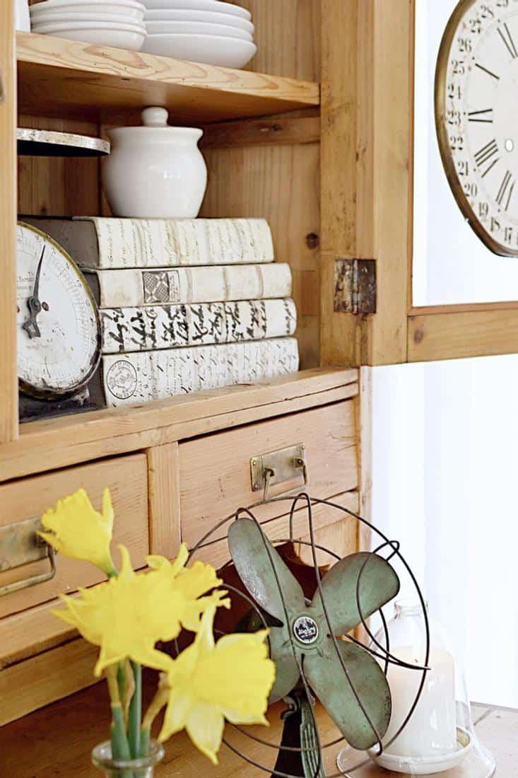 Vintage fan, scale, books, clock in an old wooden hutch.