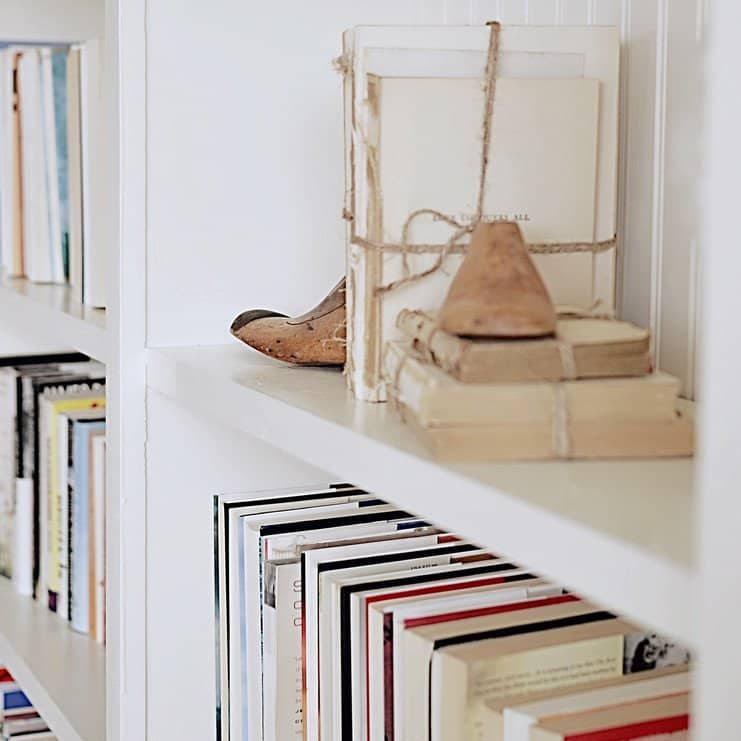 Vintage shoe stretchers and vintage books in built-in shelves.