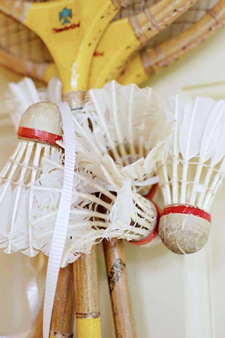 4 Vintage badminton racquets with 5 vintage birdies wrapped around the racket's neck.