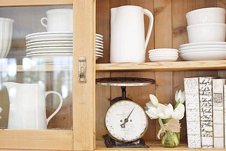 Vintage wooden hutch with white pottery, vintage scale, tulips, and books.