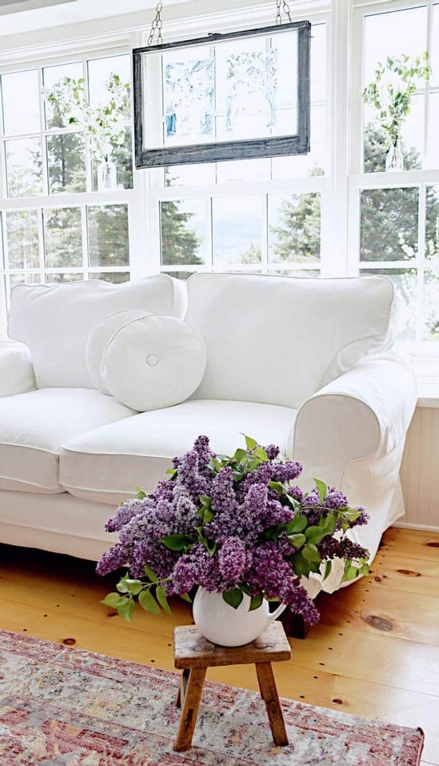 Sunroom windows with vintage hanging window with white flowers in jars and white loveseat.