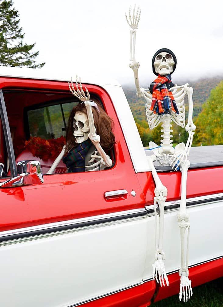 Halloween skeletons in the fog in vintage truck.