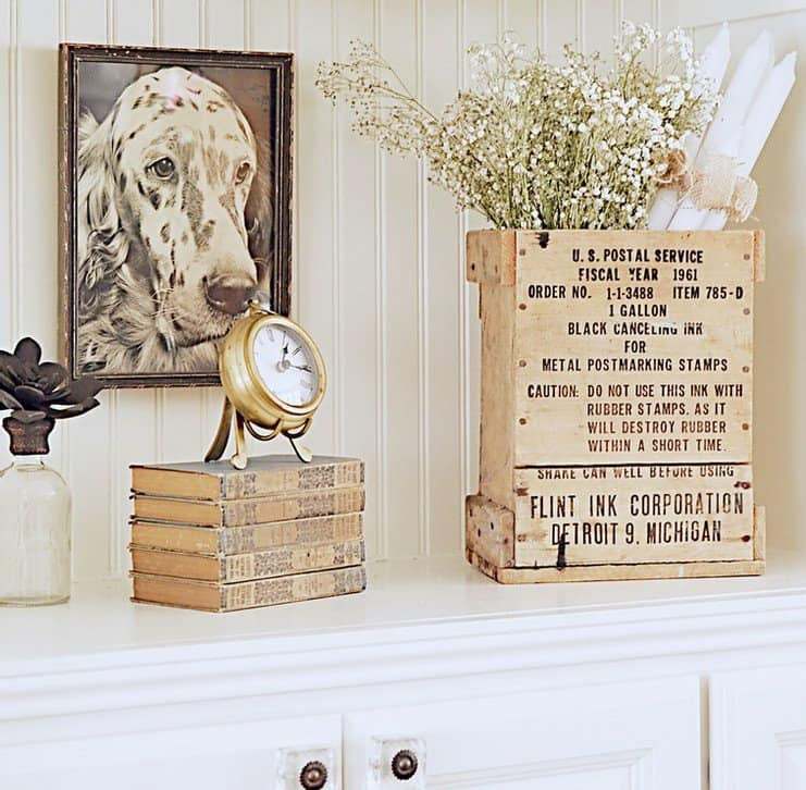 Vintage books, clock, postal box, bottle, picture and more on a built-in shelf.