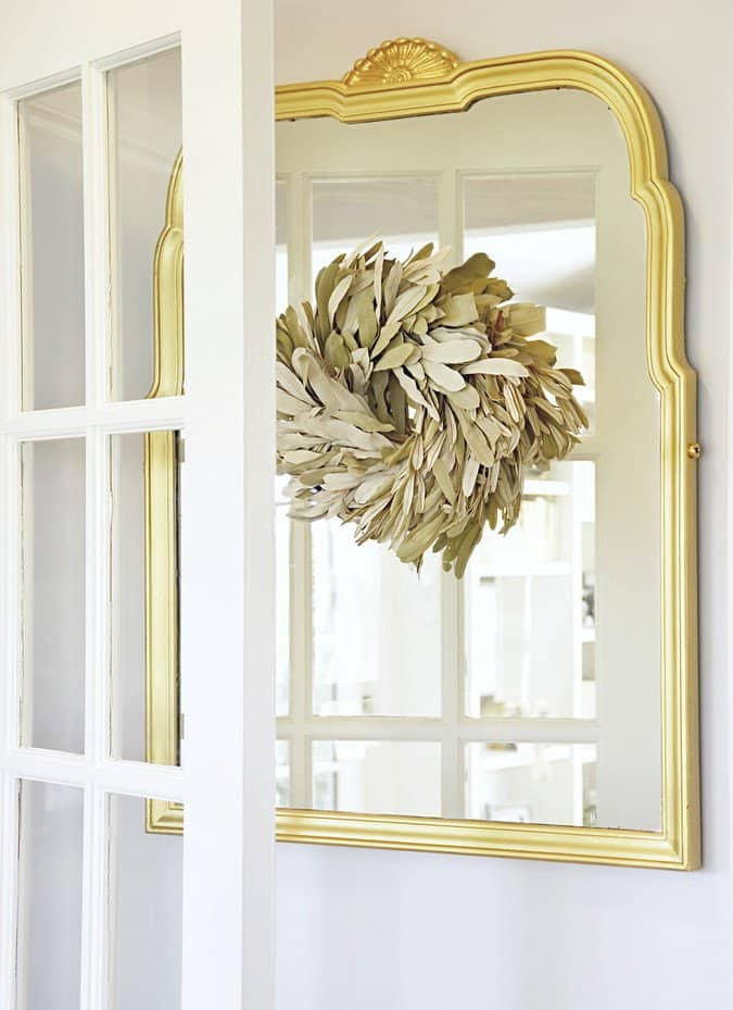 Vintage gold mirror with neutral wreath.