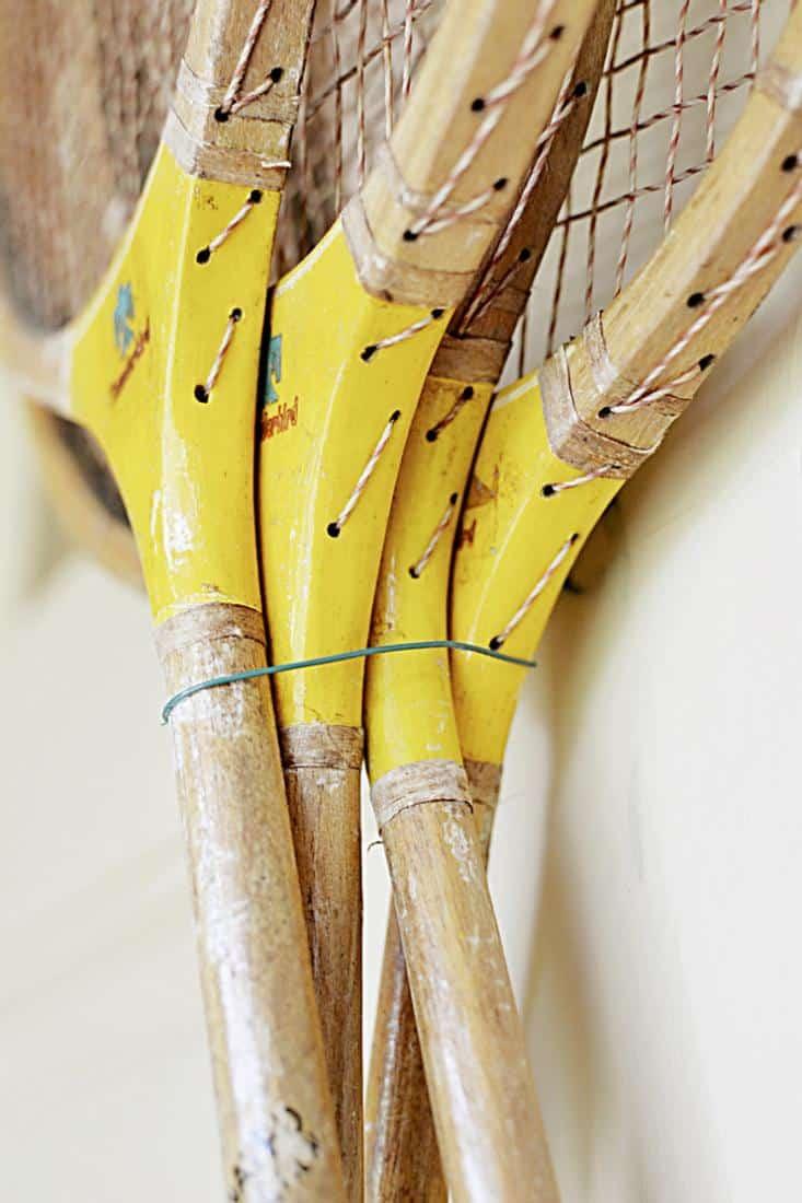 4 Vintage badminton racquets hanging with wire on front door.