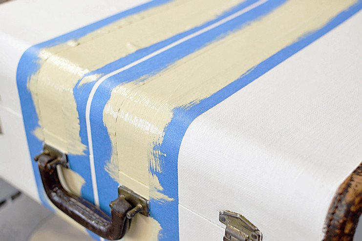 Vintage suitcase with painters tape with yellow stripes.