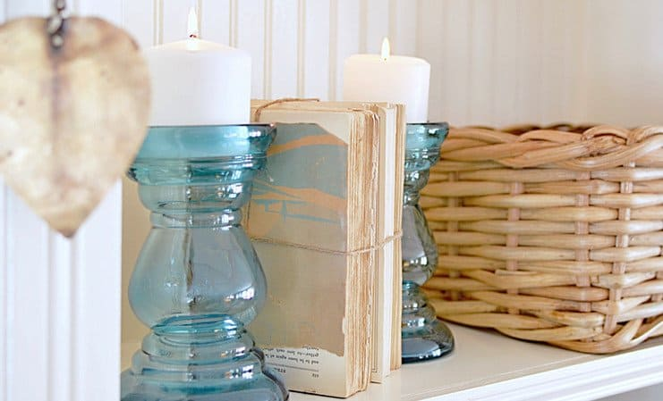 Vintage books with blue glass candlesticks and basket on shelf.