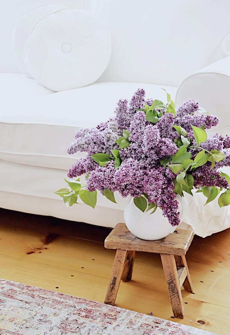 white loveseat with retro white pillows and a bouquet of lilac flowers on a vintage wooden stool.