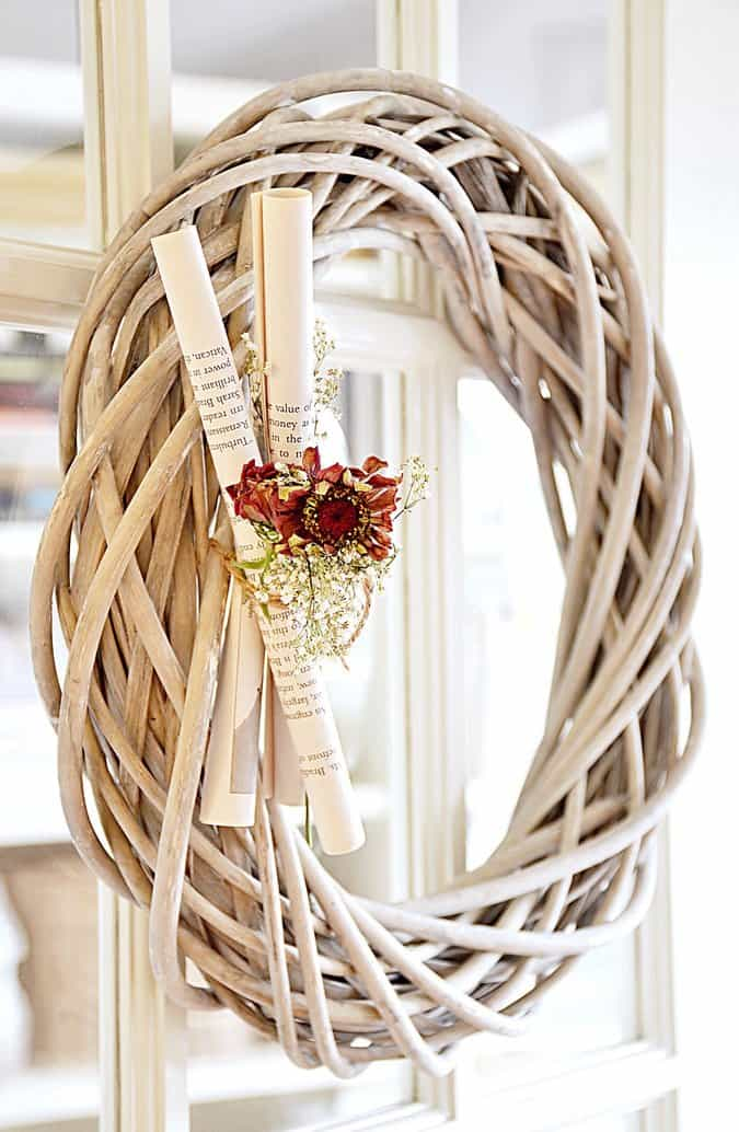 Wooden wreath with book pages and flowers.