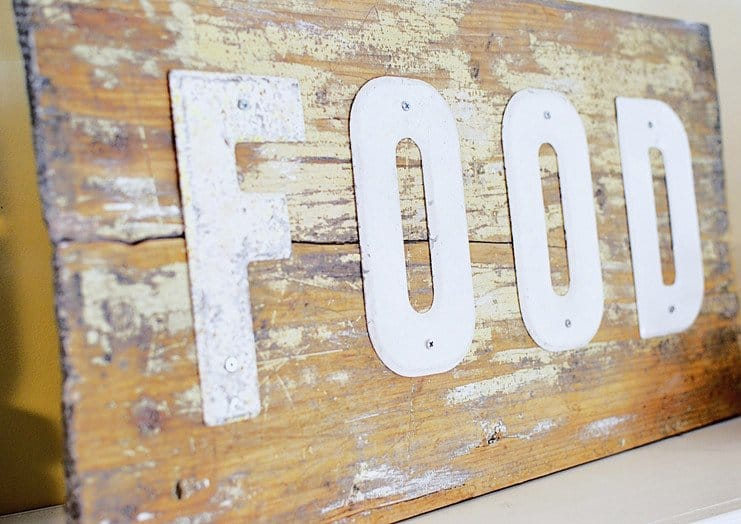 A vintage wooden sign with FOOD spelled out in white enamel.