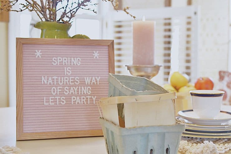 Pink felt letter board, berry boxes, china and green vase on white dining room table.