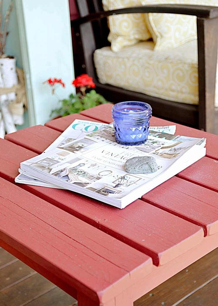 Table with magazines and candle on the porch.