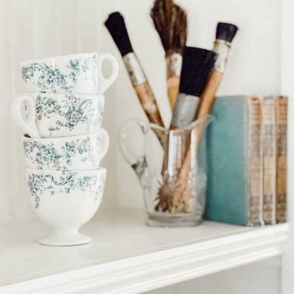 teacups, paintbrushes, and books on a bookshelf