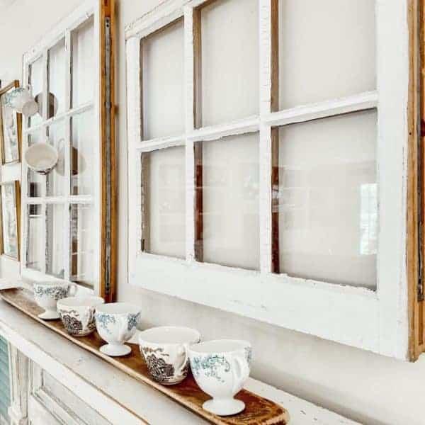 Vintage windows and teacups on a mantel