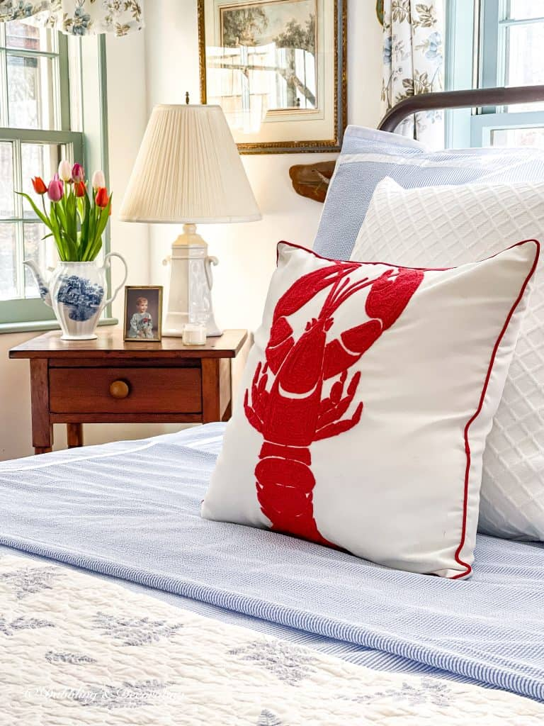 Coastal Bedroom with lobster pillow and bedside table with spring tulips.