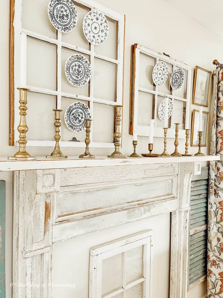 Faux vintage mantel with old windows and hanging plates.