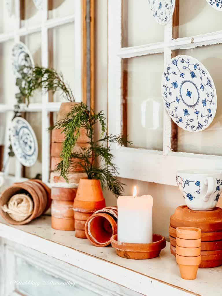 Terracotta pots scattered on a mantel.