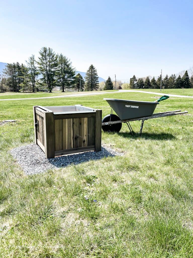 Wooden Fire Pit and Wheelbarrow on top of a grass covered field