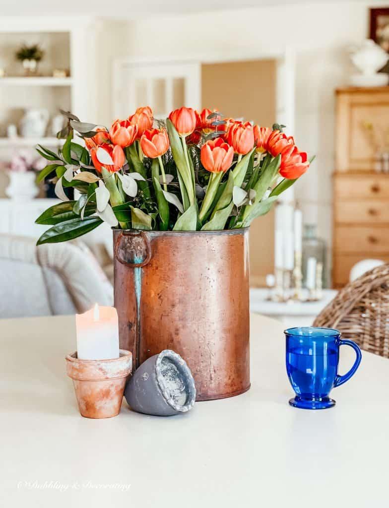 Copper bucket with orange tulip arrangement.