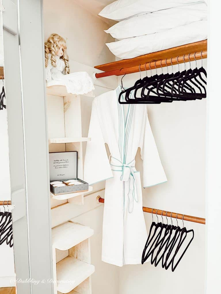 Black Velvet Clothes Hangers in guest bedroom closet with bathrobe.