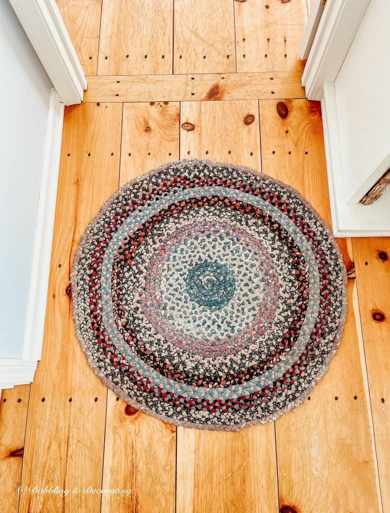 A braided rug on a wood floor