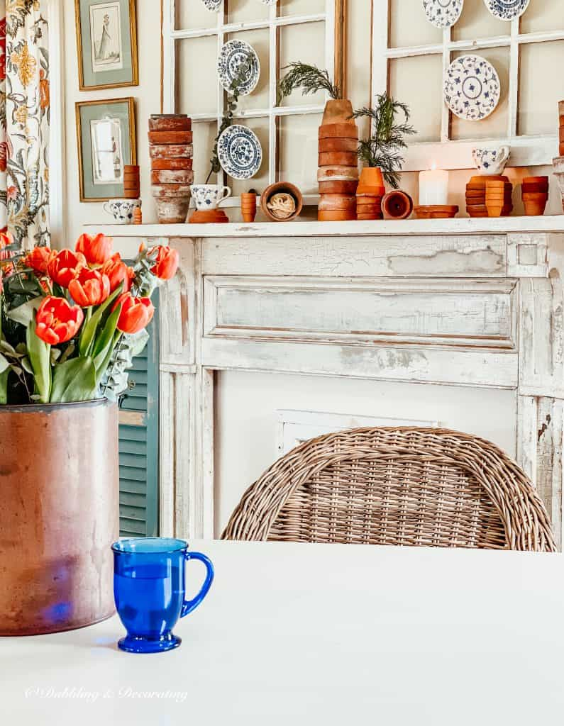 Vintage Mantel with stacked terracotta pots and a bucket of tulips.