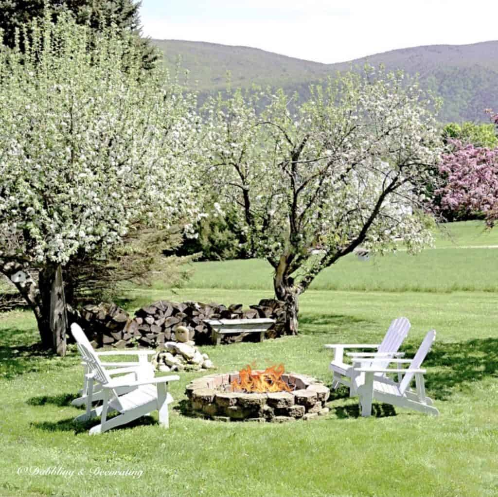 Spring Backyard Vermont view with fire pit and Adirondack chairs.