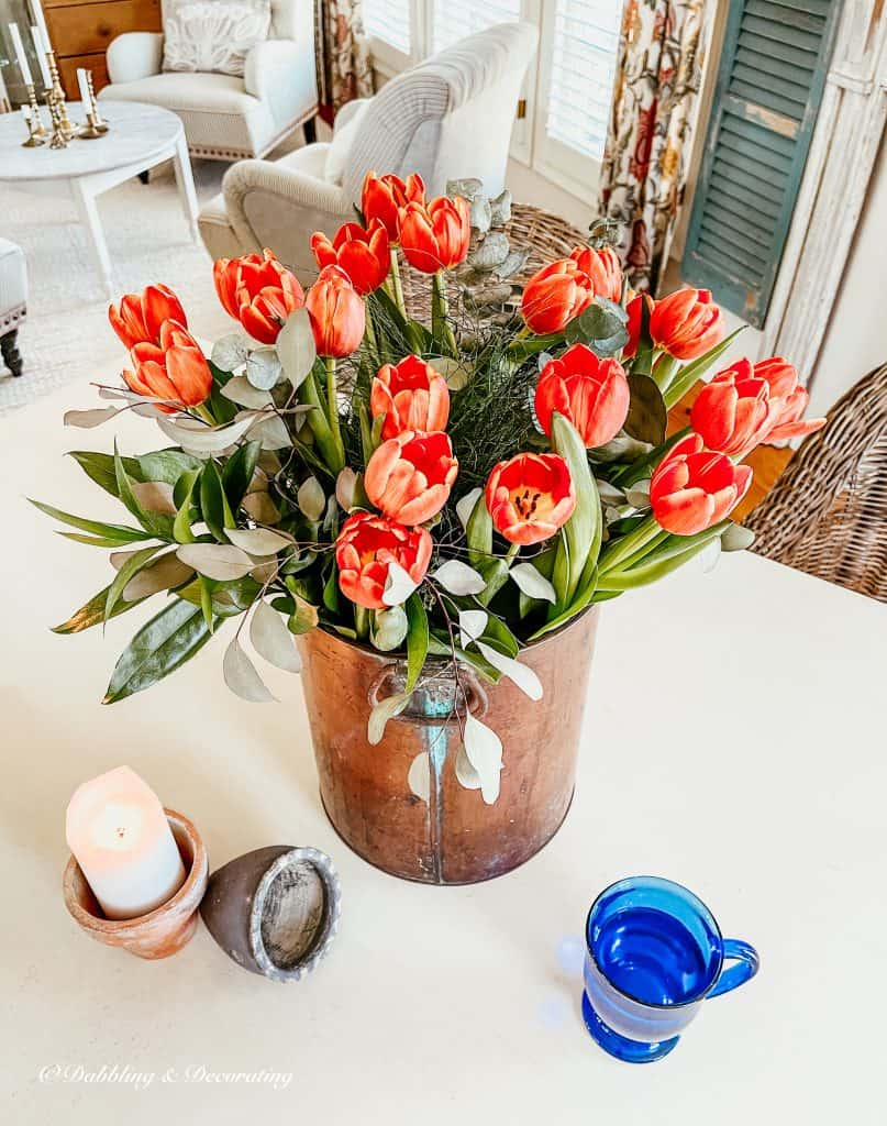 Bouquet of orange tulips in a copper bucket on the table.
