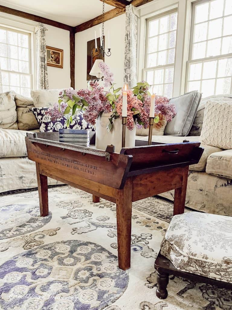 Antique coffee table decorated with lilacs.