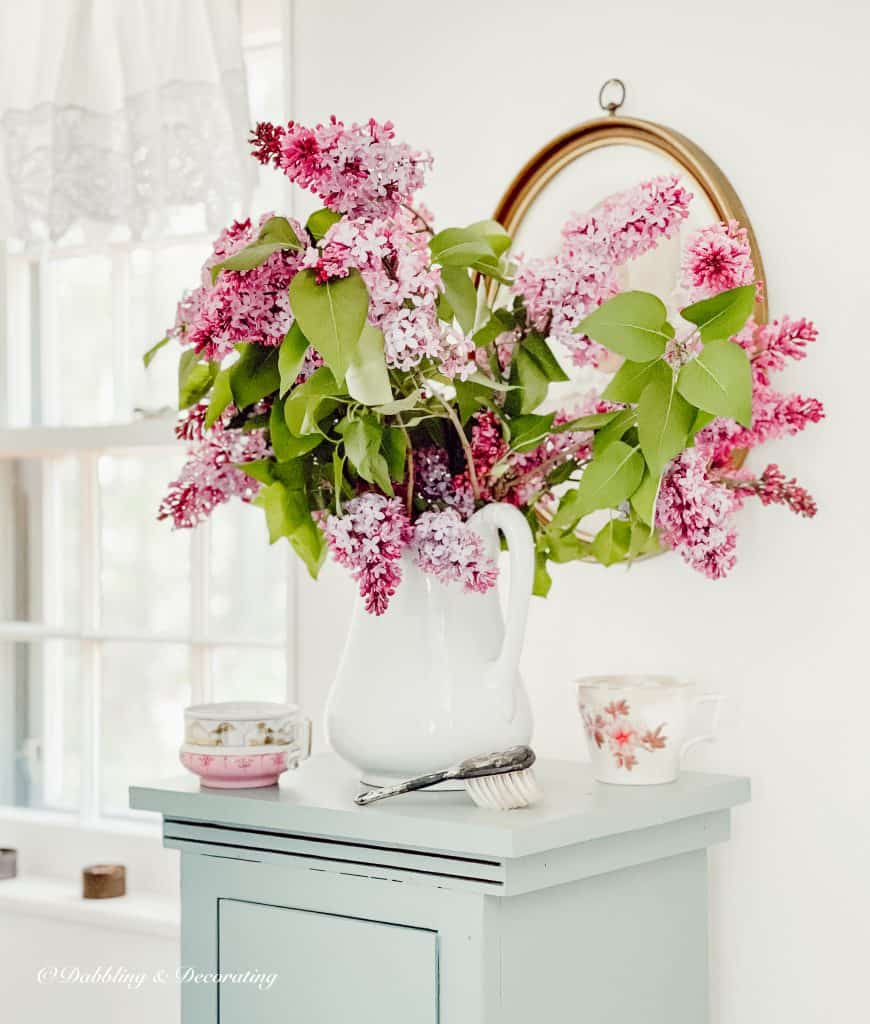 Lilacs on a blue cupboard in the bathroom.