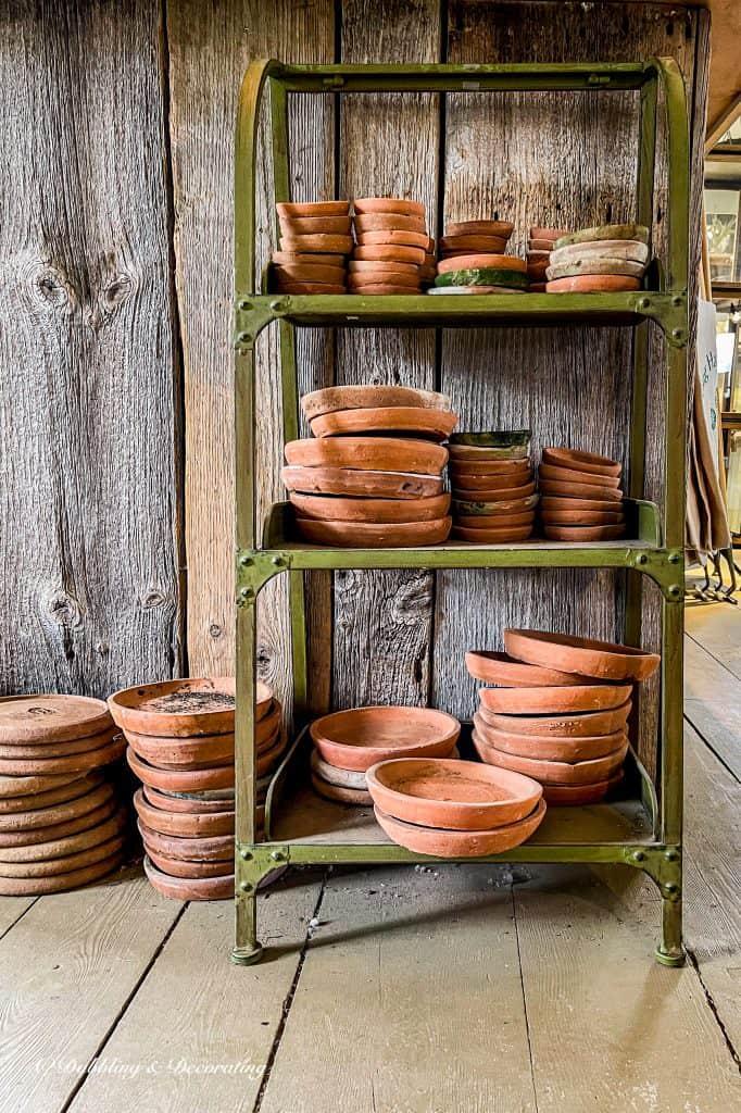 Terracotta pots on a green rack