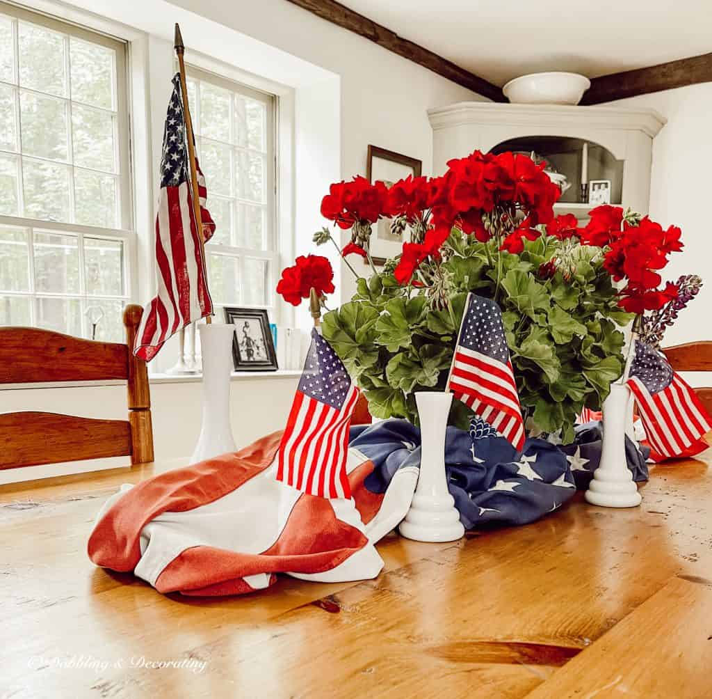 Red geraniums, flags dining room centerpiece.