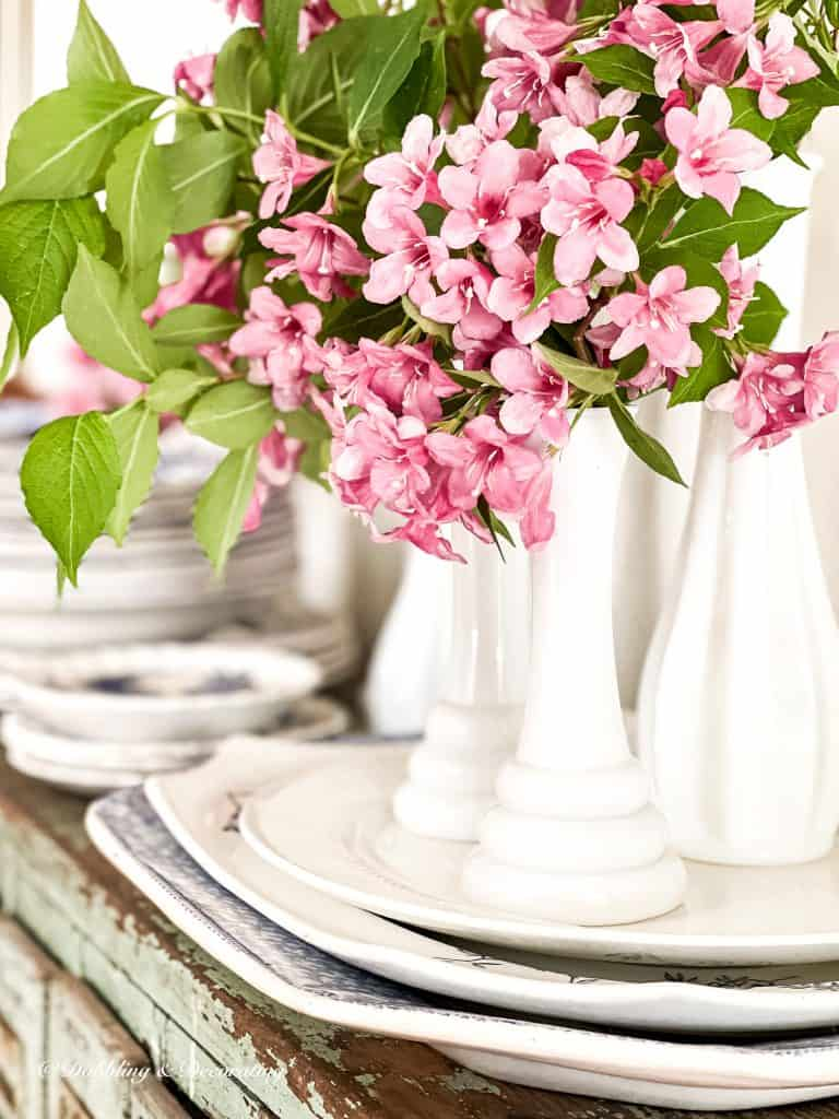5 Clever Ways to Decorate with Yard Sale Finds.  Milk glass bud vases with pink flowers and dishes.