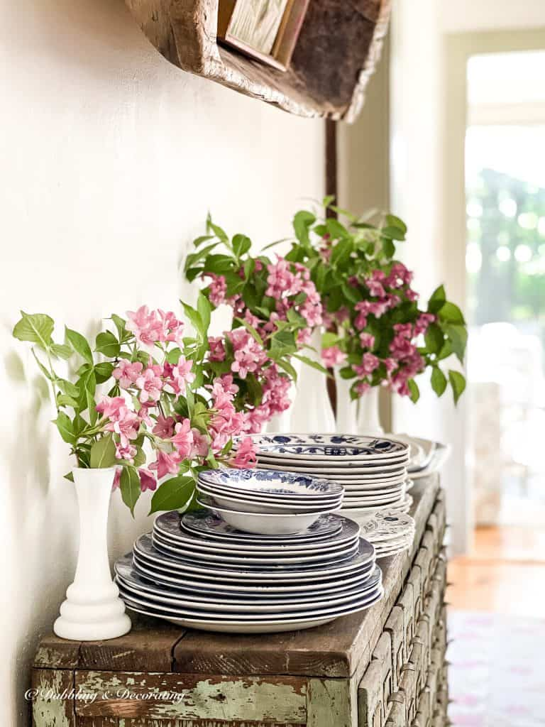 5 Clever Ways to Decorate with Yard Sale Finds.  Stack of dishes and pink flowers.