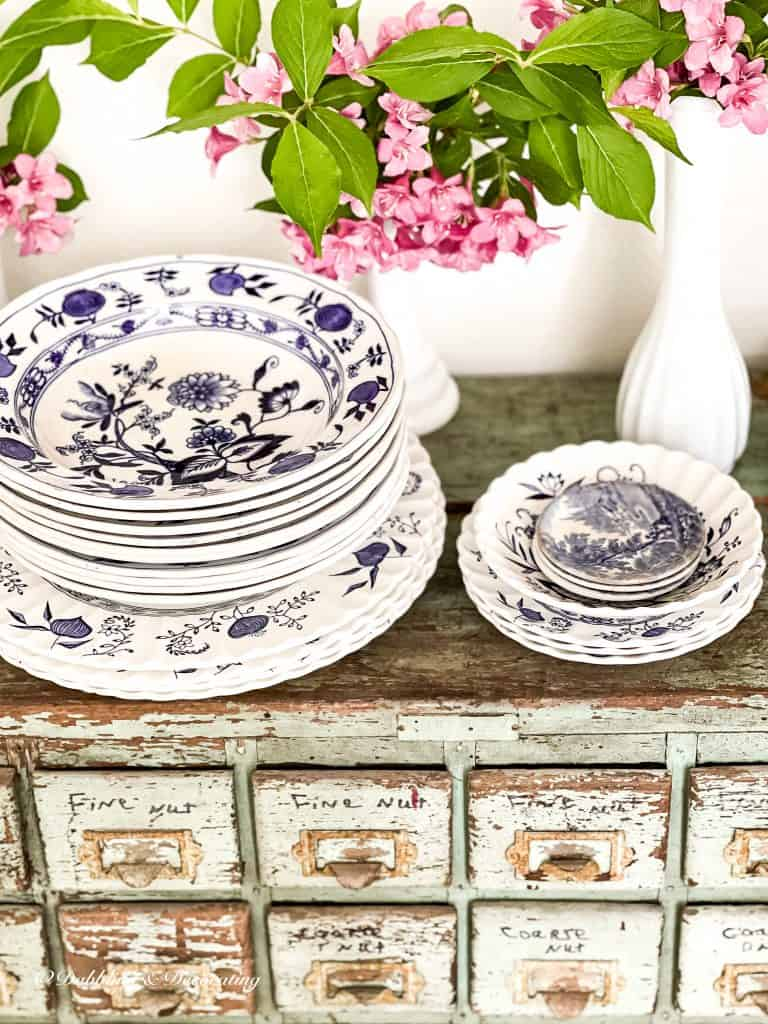 5 Clever Ways to Decorate with Yard Sale Finds.  Stack of blue and white dishes and pink flowers.