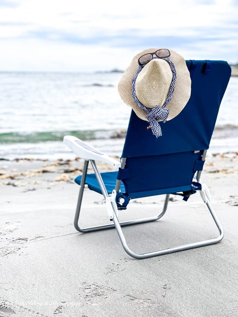 My Favorite Beach Day Essentials.  Beach chair with hat and sunglasses.